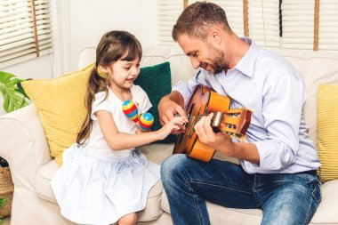 Father with little daughter having fun and playing guitar together on the sofa at home.Love of family and father day concept