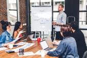 Skupina neformální obchodní setkání a diskusi s notebookem computer.creative podnikateli prezentace a plánování v moderní workloft. Koncepce týmové práce