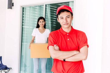 Woman accepting a delivery boxes from delivery man in red uniform.courier service concept