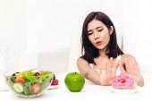 Fotografie Žena rozhodování mezi kalorií bomba čokoládová kobliha a zdravý salát. Žena odmítá deska s nezdravým kobliha doma. Zdravé stravování, diety a nezdravé jídlo koncept