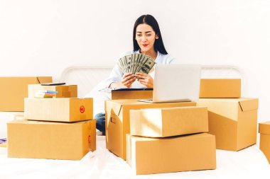 Young woman freelancer working and holding money with cardboard box on bed at home - SME business online and delivery concept