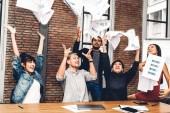 erfolgreiche Gruppe von Casual Business entspannen und werfen Papier in moderne Arbeit loft.creative Geschäftsleute feiern mit den Armen nach oben .Teamwork und Erfolgskonzept