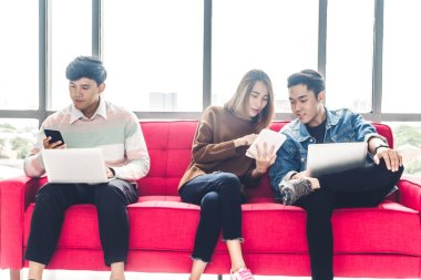 Group of business sitting relax use technology together of smartphone and laptop computer checking social apps and working.Communication concept
