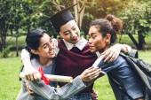Sikeres a tanuló fiatal nő és a bachelor ruhák oklevelek diplomás átölelve barátja Egyetemen. Érettségi és oktatási koncepció ünnepli