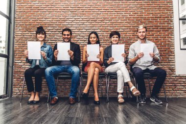 Group of business people holding paper while sitting on chair waiting for job interview against wall background