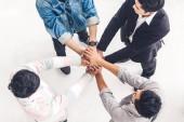 Pohled shora úspěšné skupiny podnikání lidí zásobníku a dát ruce dohromady v kanceláři. Koncepce týmové práce přátelství