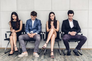Group of business people sitting on chair waiting for job interview against wall background