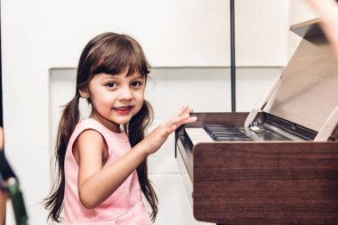 Little girl playing the piano in living room at home