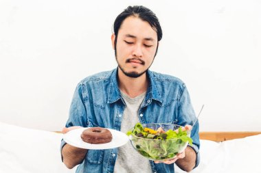 Man holding and making choice between healthy salad and calorie bomb chocolate donut on bed at home.Healthy eating and Junk food concept