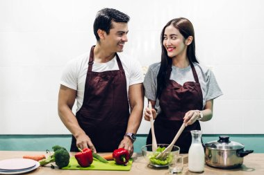 Happy couple cooking and preparing meal together in the kitchen