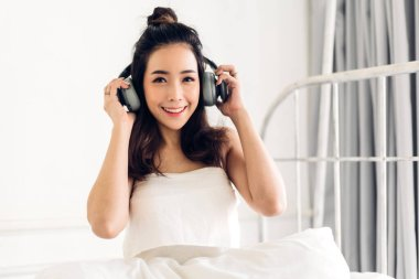 Beautiful young asia woman relaxing listening to music with  hea