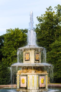 Roman style cascading fountain in the Park against green trees and blue sky