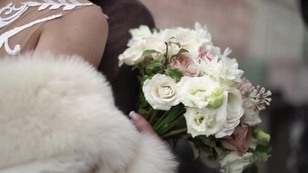 Bride with wedding bouquet embracing groom