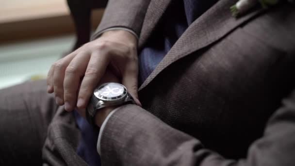 Man in brown suit looking at wrist watches