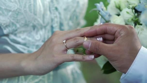 Bride and groom put on wedding rings