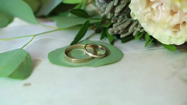 Dva zlaté snubní prsteny na mramorové pozadí