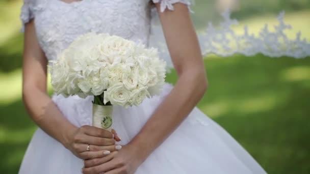 Fiatal gyönyörű menyasszony fehér esküvői ruha nyári nap a parkban tartózkodó Fehér Rózsa csokor