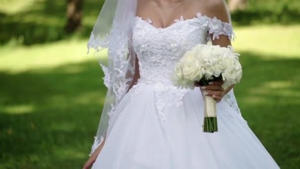 Mladá krásná nevěsta ve svatební bílé šaty s kytici bílých růží, ubytovaní v parku v letním dni