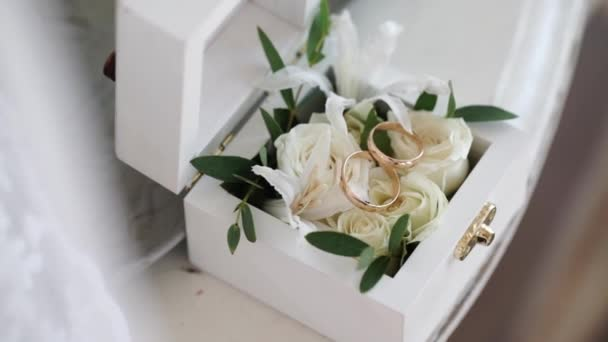 Two golden wedding rings in a white wooden box with rose flowers