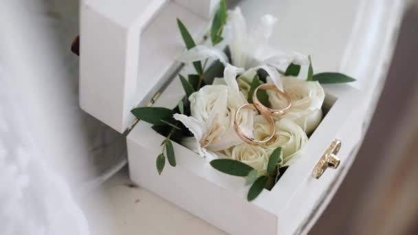 Dva zlaté snubní prsteny v bílé dřevěné krabici s květy růže