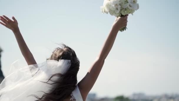 A virágok csokor az ablakban fogását egy tetőtéri kezeket fel tartózkodó fiatal menyasszony