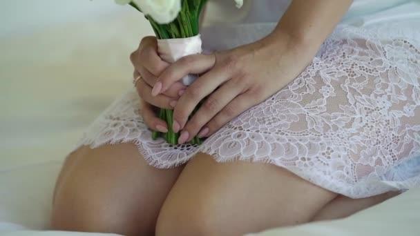 Silná dívka v bílém prádle sedí na posteli s svatební kytice s bílou růží