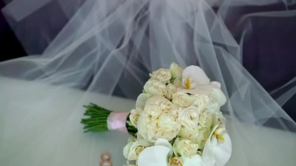 Bridal wedding bouquet of white roses on veil and two wedding rings