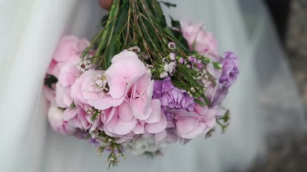 Bride holding flowers bouquet with violet flowers