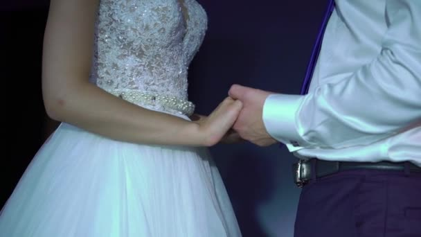 Nevěsta a ženich, drželi se za ruce na večírku