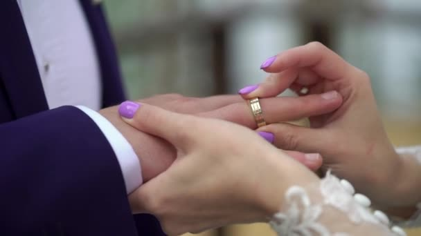 Bride putting a ring on grooms finger during wedding ceremony