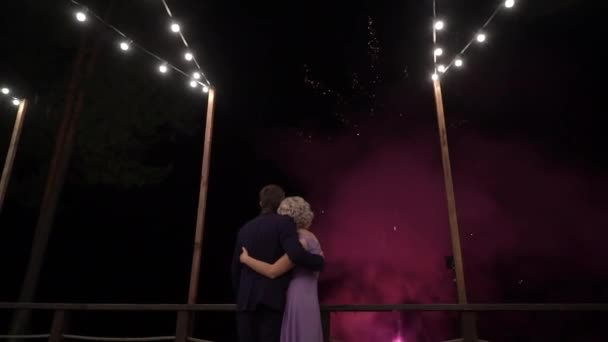 Couple of beautiful stylish newlyweds looking at fireworks exploding in the night sky on their wedding day
