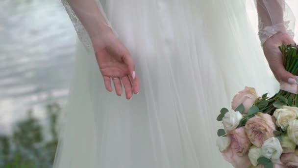 nevěsta drží kytici za jejími zády