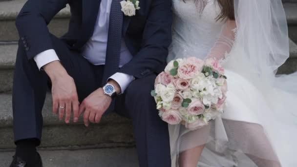 Šťastný svatební pár sedí na schodech venku