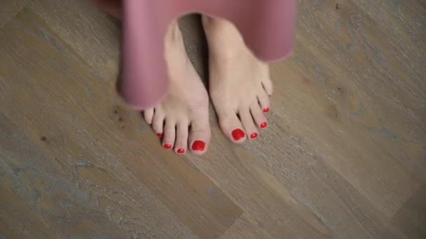 Piedini delle donne con pedicure rosso. Womens piedi soggiornare e andare a piedi nudi sul pavimento a casa