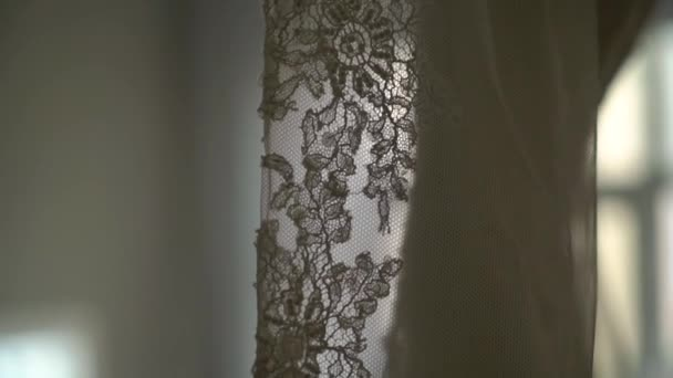 0ef0e6028a Luxury wedding dress hanging in bedroom. Silhouette of amazing brides lace  gown in light. Morning preparation