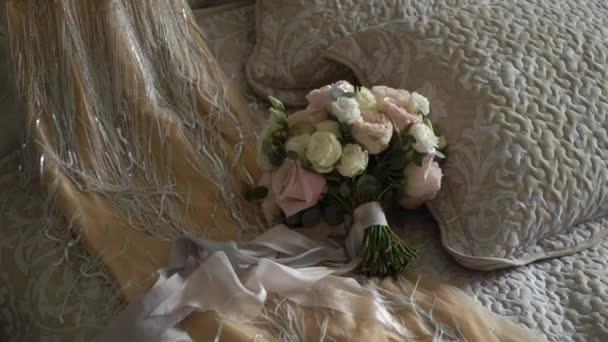 Svatební šaty a kytice květin v ložnici