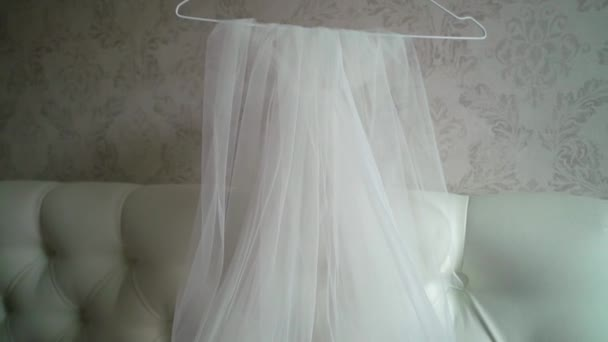 Bridal wedding white veil on bed in brides bedroom