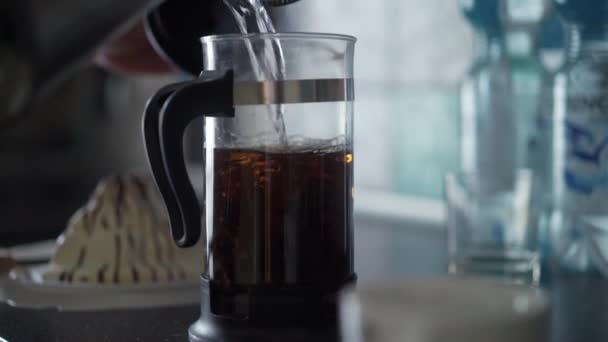 French press with hot tea in light slowmotion. Beautiful tea leafs in glass teapot.