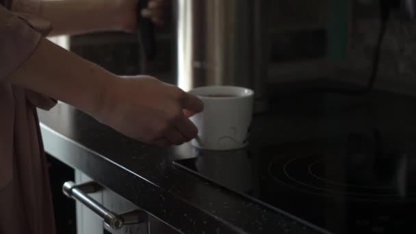 Skleněná konvice nalévá čaj v bílém cup v kuchyni. Čas na snídani v dopoledních hodinách. Mladá sexy žena v neglegee s hrnkem čaje