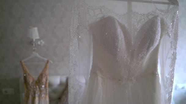 94e45d65a8 Two luxury wedding dress hanging in bedroom - white and golden. Silhouette  of amazing brides lace gown in light. Morning preparation
