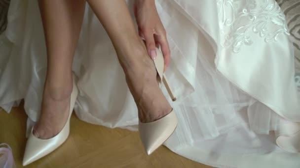 Braut setzt auf Hochzeitsschuhe an ihren zarten Füßen