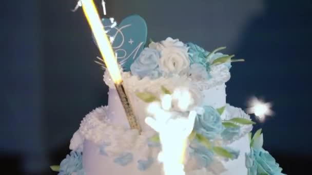 Svatební dort s ohňostrojem stojí na stole v restauraci