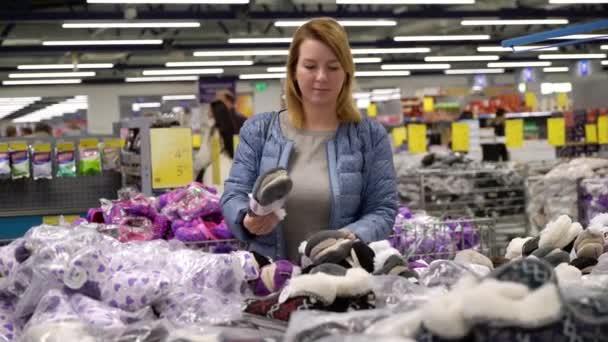 Mladá žena nakupovat v hypermarketu. Výběr bot v obchodě