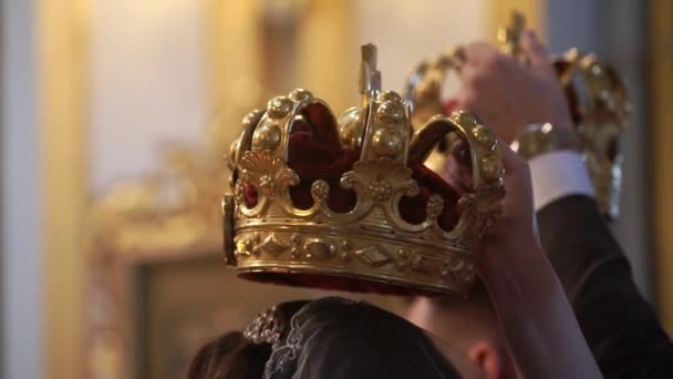 Crowns for wedding in church. Newlyweds at ceremony, priest praying