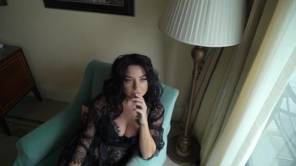 Giovane donna brunetta sexy in lingerie che si siede sulla sedia in camera da letto e in posa.