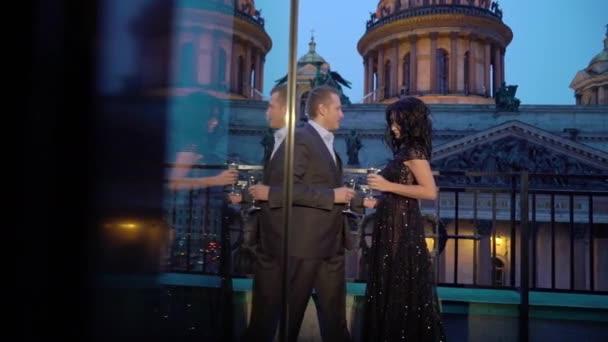 Junge Caucasican Mann in Anzug und sexy Brünette Frau in schwarzem Luxus Kleid am Balkon in einer Stadt wohnen