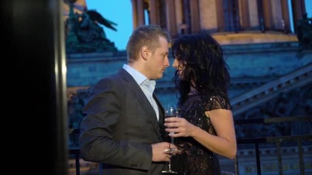 junger kaukasischer Mann im Anzug und sexy brünette Frau im schwarzen Luxuskleid, die nachts auf einem Balkon in einer Stadt verweilt. Flirten oder schöne Paare auf der Hotelterrasse mit Gläsern Champagner. Zeitlupe.