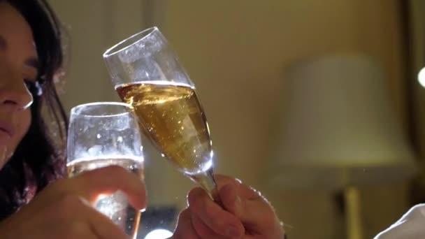 junges sexy Paar liegt nachts in weißen Bademänteln im Schlafzimmer und trinkt Champagner aus Gläsern.