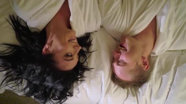 Junge sexy Paar in der Nacht liegen im Schlafzimmer in weißen Bademänteln und Spaß haben. Lächeln und lachen