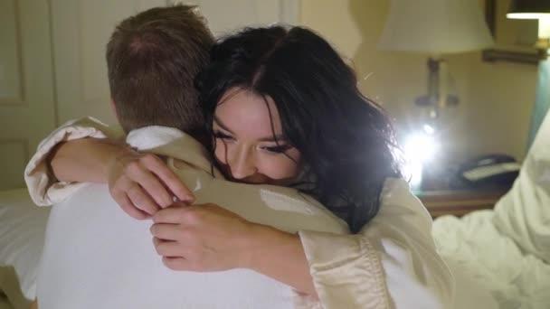 Giovane coppia sexy di notte posa in camera da letto in accappatoio bianco e che abbracciano prima del sesso. Appuntamento romantico della giovane donna e uomo